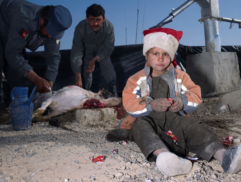 Mark Neville, Child, Jacket, Slaughtered Goat, Sweets, Painted Nails, Xmas Day, Helmand, 2010, Courtesy of the artist and the Imperial War Museum.