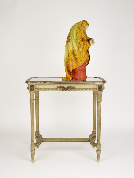 The Misanthrope, 2011, Modelling material, foil, wire, acrylic paint, silk, wood, polyester padding, nylon, costume jewellery, found table, (figure) 59 x 25 x 30 cm, (table) 80 x 80 x 53 cm