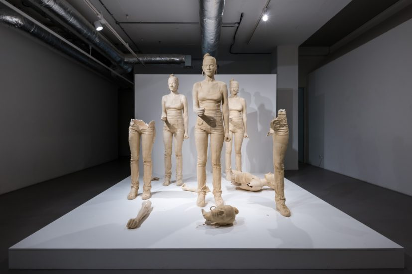 Simon Fujiwara, Rebekkah (2012), five figures, from an edition of 3 (+ 2AP), terra-cotta dyed, life sized, cast plaster female figures with accompanying video (7mins 33 secs). Presented to Leeds Art Gallery by the Contemporary Art Society through the Collections Fund, 2013. Photo by Joe Plommer