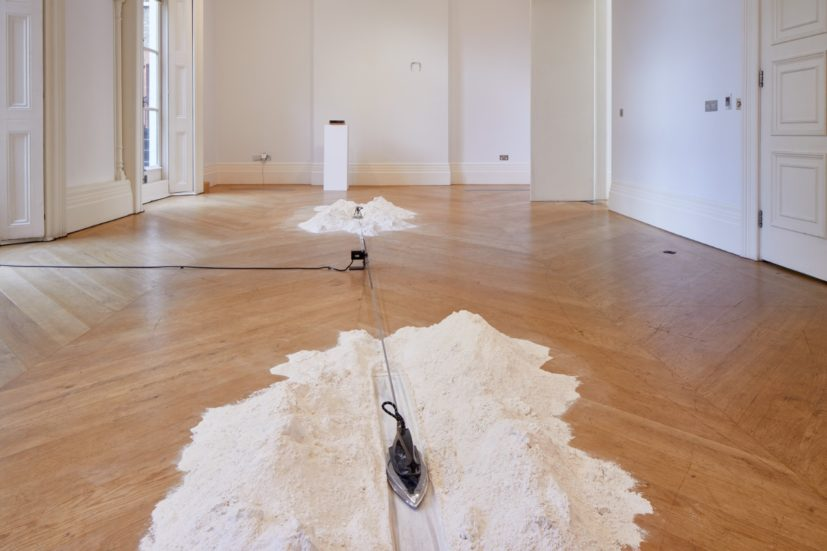 Pascal Hachem, back to square one, 2017. Irons, flour, metal structure, step motor and electrical board. Photograph by Andy Stagg, courtesy of The Mosaic Rooms.