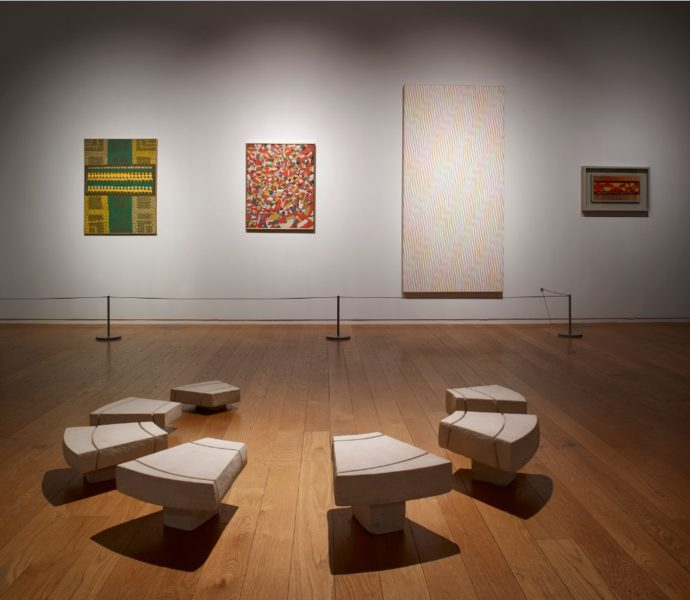 Installation view of 'Speech Acts' at Manchester Art Gallery. Works (L-R on wall): Anwar Jalal Shemza, War Sonnet, 1969; Fahrelnissa Zeid, Red Composition, 1959; Bridget Riley, Zephyr, 1976; Anwar Jalal Shemza, One to Nine and One to Seven, 1962. In foreground: Kim Lim, Spiral II, 1983