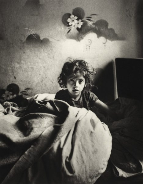 Roman Vishniac, 'Sara, sitting in bed in a basement dwelling, with stenciled flowers above her head, Warsaw', ca. 1935–37. © Mara Vishniac Kohn, courtesy International Center of Photography. On display at The Photographers' Gallery