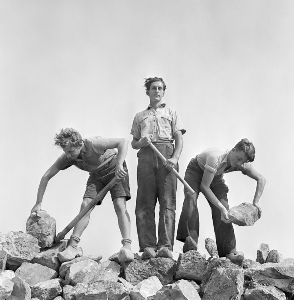 Roman Vishniac, 'Ernst Kaufmann, center, and unidentified Zionist youth, wearing clogs while learning construction techniques in a quarry, Werkdorp Nieuwesluis, Wieringermeer, The Netherlands', 1938–39. © Mara Vishniac Kohn, courtesy International Center of Photography. On display at Jewish Museum London