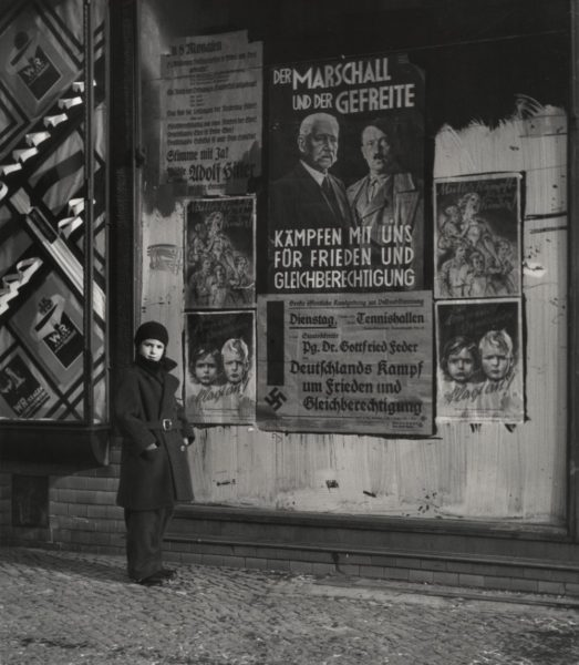 Roman Vishniac, 'Vishniac's daughter Mara posing in front of an election poster for Hindenburg and Hitler that reads
