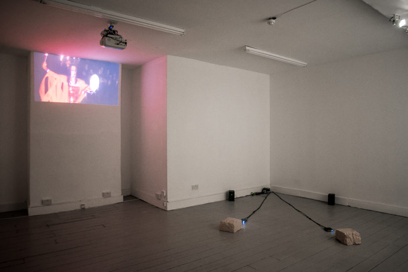 Installation view. (left) Kent Monkman, Iskootāo 2010, video, Kent Monkman in collaboration with Gisèle Gordon; and (right) Leah Capaldi, Shooting and Fishing, 2018. 2 channel video sculpture projectors, video, speakers, media players, plasticine, excerpt from McLintock! Photo Katarzyna Perlak